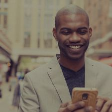 sharp black man looking at phone. used for 2016 tech outlook